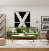 green sofa black armchairs mid century modern house white carpet on wooden floor wooden bookcase on the side