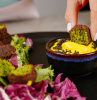 half of falafel dipped into yellow dip with black sesame seeds vegan finger food black dip bowl placed on black plate