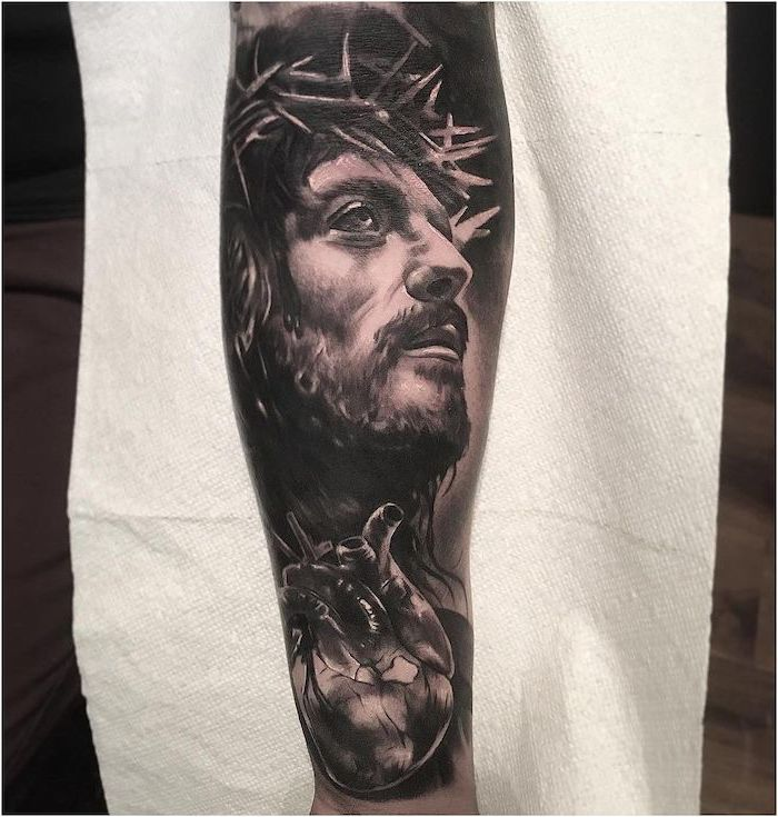 half sleeve tattoo of jesus looking up anatomical heart underneath tattoo ideas with meanings white paper in the background