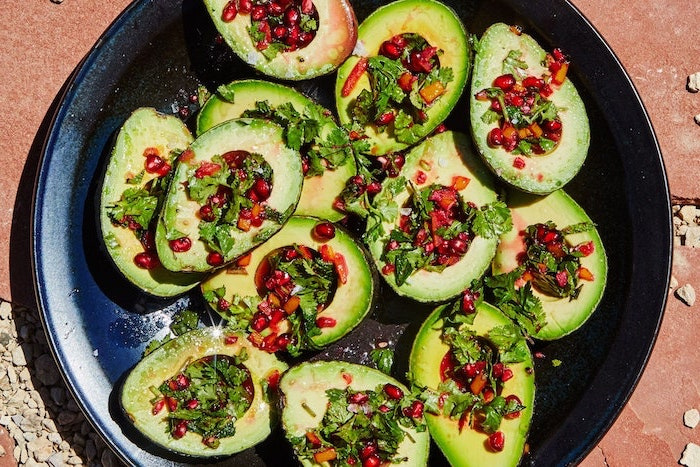halved avocados filled with chopped parsley pomegranate seeds arranged on black plate vegan appetizers