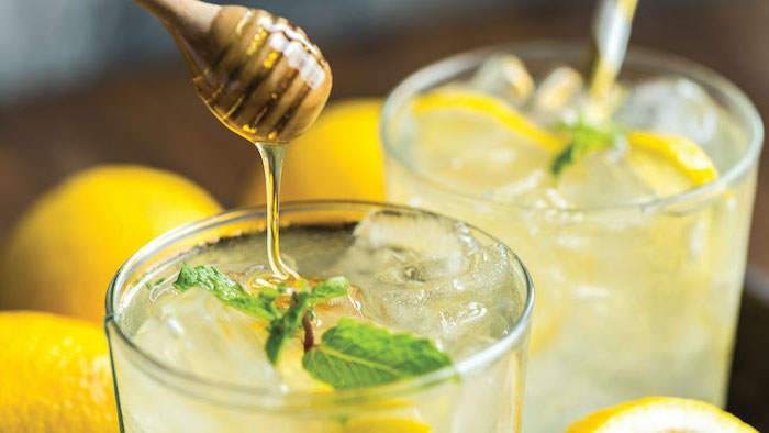 honey being poured into glass with lemonade ice and mint leaves detox drinks lemons on the side