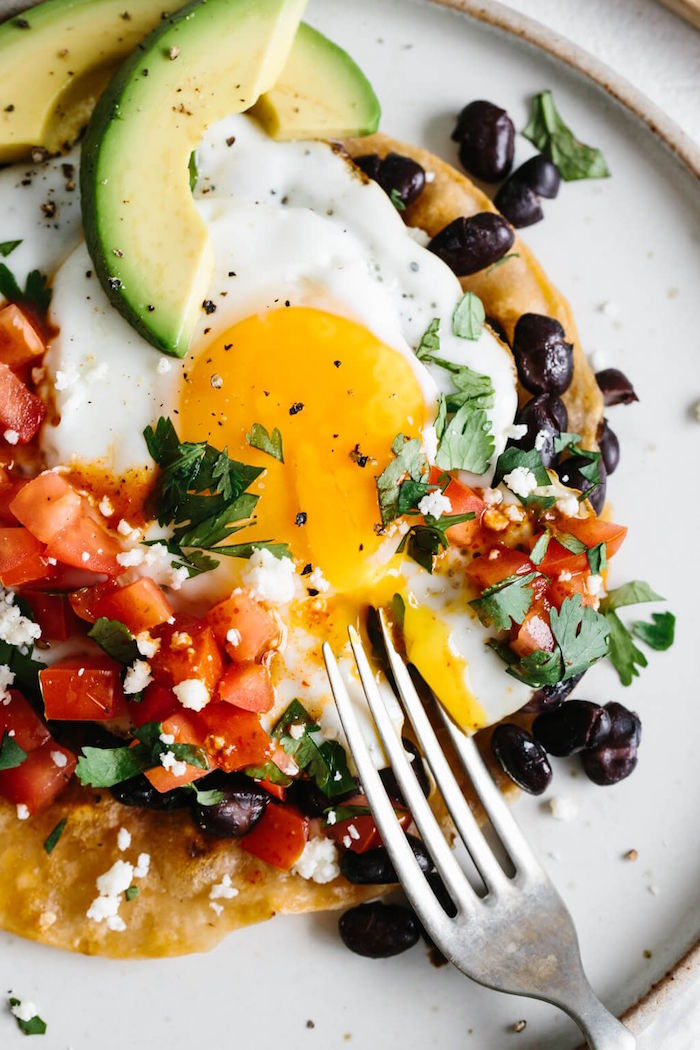 huevos rancheros on white plate mexican dinner ideas with chopped tomatoes black beans parsley crumbled feta cheese