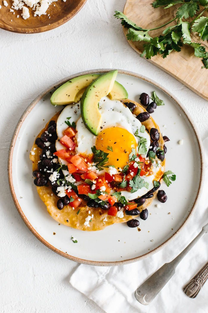 huevos rancheros with tomatoes black beans chopped parsley crumbled feta cheese mexican dinner ideas slices of avocado