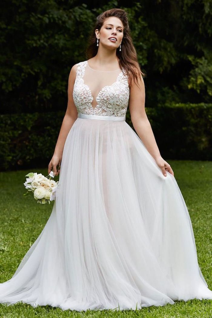 lace top with tulle bottom white boho wedding dress worn by brunette woman holding small white flower bouquet