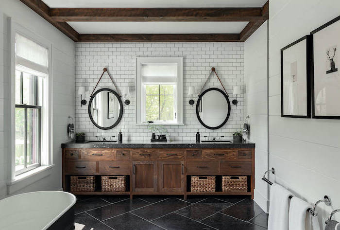 large wooden vanity with two sinks two mirrors mounted on wall covered with subway tiles farmhouse bathroom ideas black tiles on the floor