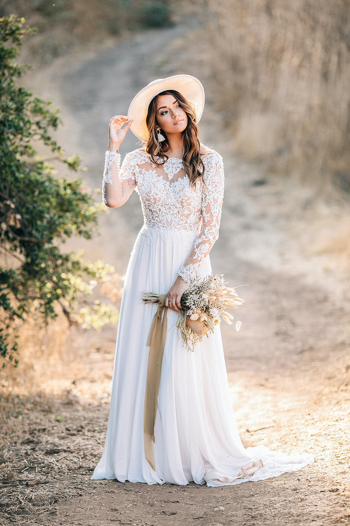 long sleeve boho wedding dresses woman with medium length wavy hair wearing dress with lacy top and lacy long sleeves bottom skirt made of tulle