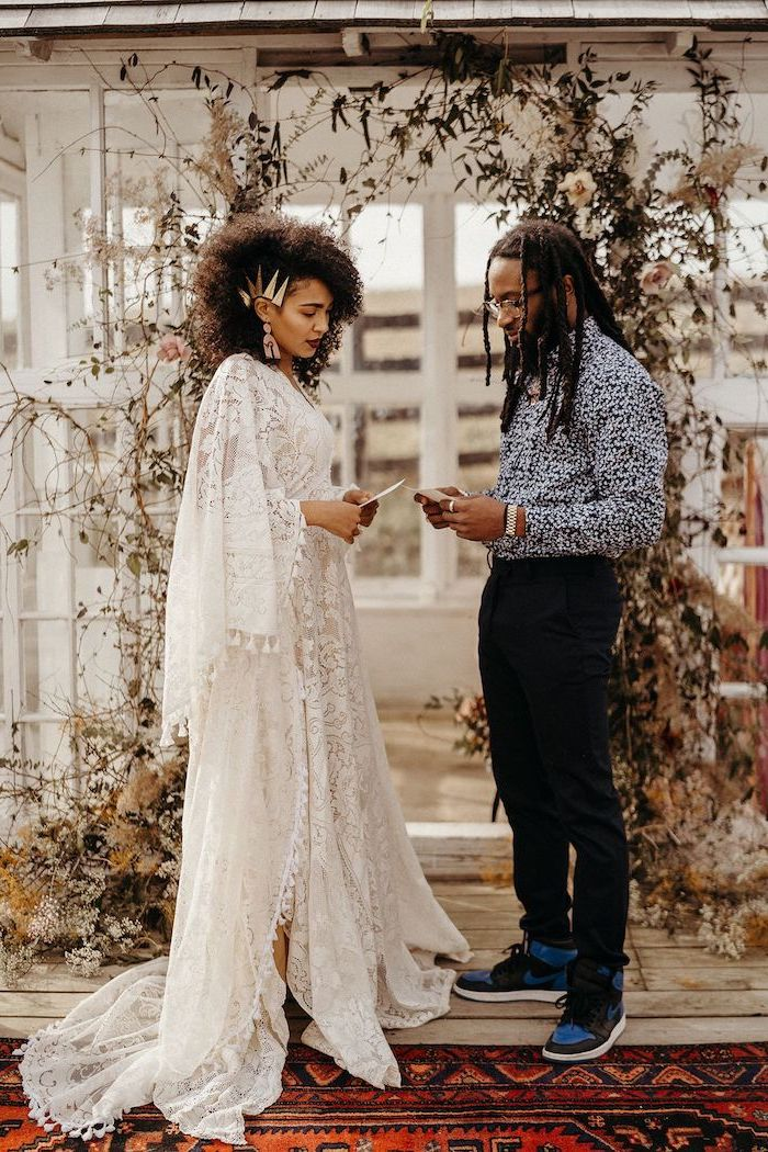 man and woman standing at the altar boho wedding dress woman wearing all lace white dress with wide sleeves man wearing black pants floral shirt