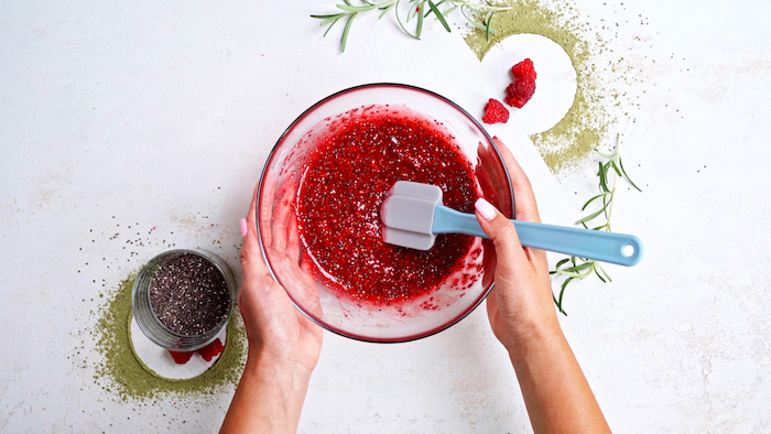 mashed raspberries with chia seeds added to it in glass bowl easy vegan appetizers placed on white surface