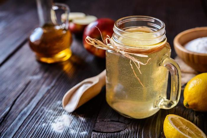 mason jar filled with apple cider vinegar and lemon juice how to detoxify your body placed on wooden surface