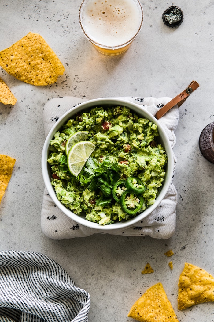 mexican dinner ideas guacamole inside white ceramic plate garnished with lime slices cilantro and chopped jalapenos