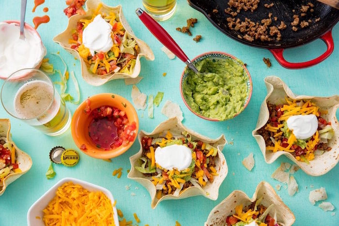 mexican dishes blue surface covered with different types of ingredients for tacos guacamole salsa glass of beer