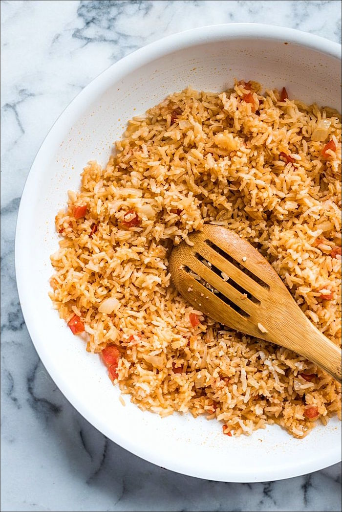 mexican rice with peppers in white ceramic bowl with wooden spatula authentic mexican recipes placed on marble surface