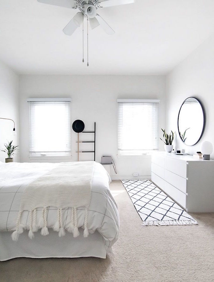 minimalistic bedroom in all white scandinavian design round mirror above a vanity white bed sheets
