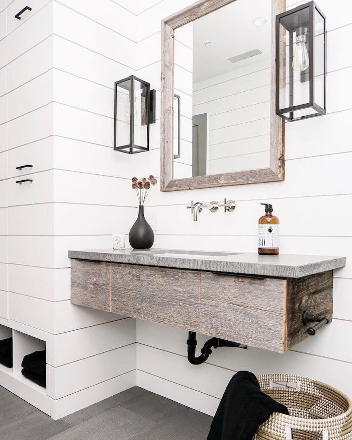 mirror hanging above floating wooden vanity modern farmhouse bathroom walls covered with white shiplap