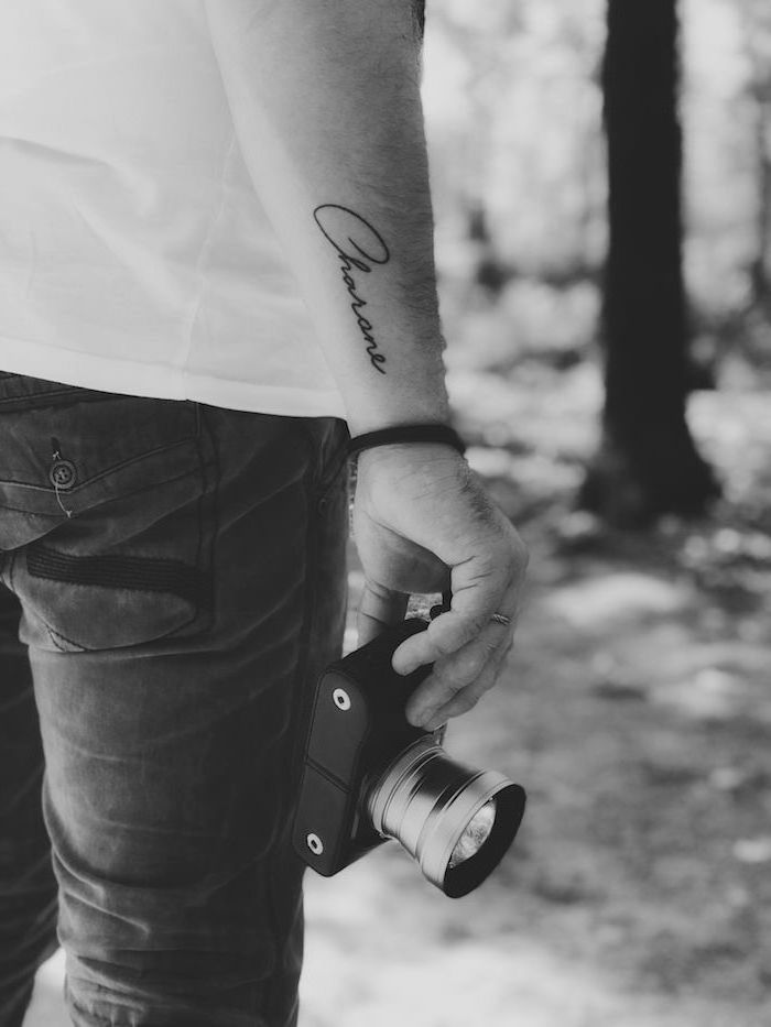 name written in cursive font on the side of the wrist on man holding camera small tattoo ideas for men black and white photo