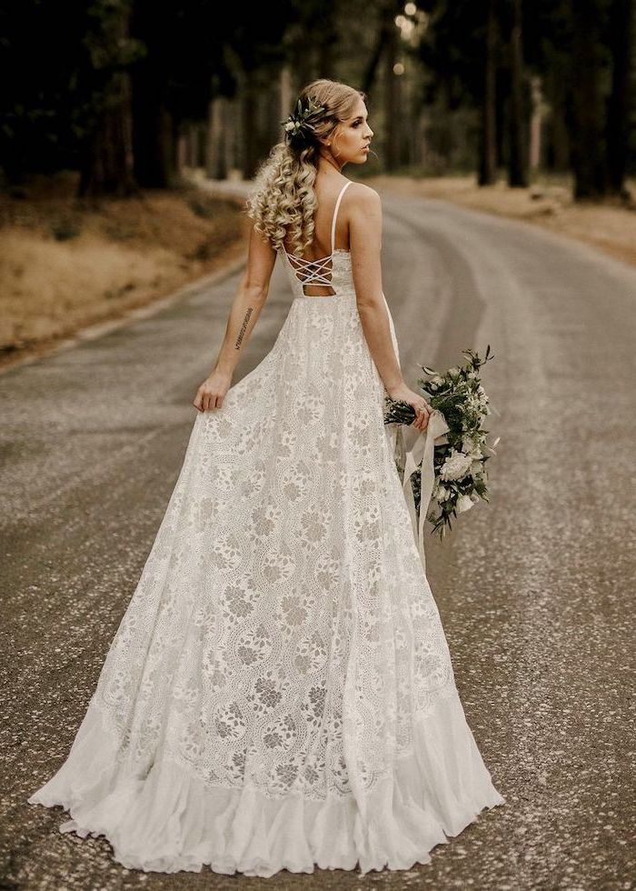 photo taken on lone road with trees unique wedding dresses blonde woman wearing all lace white wedding dress holding white flower bouquet