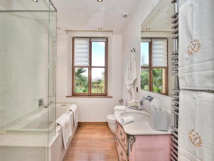 pink vintage vanity with large mirror above it farmhouse bathroom shelves wooden floor white walls