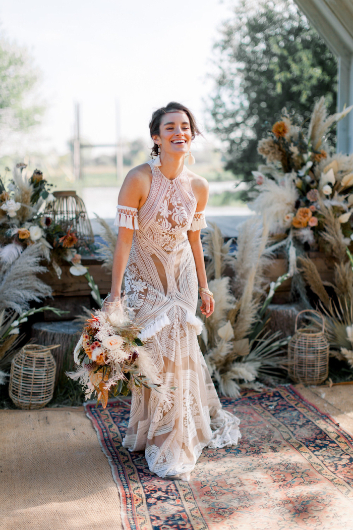 plus size beach wedding dresses brunette woman wearing a dress made of lace holding a bouquet with flowers and pampas grass