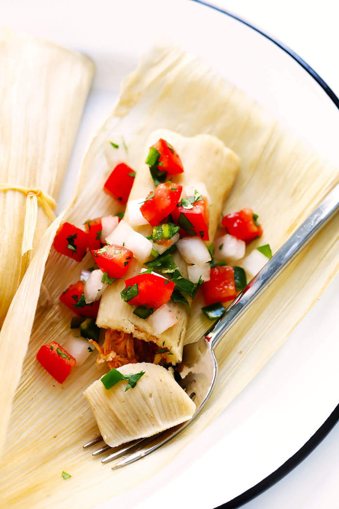 popular mexican food tamales garnished with chopped tomatoes onion parsley placed on white plate