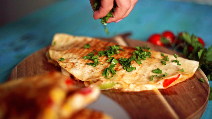 quesadilla placed on round wooden cutting board easy mexican dishes garnished with chopped parsley