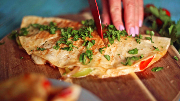 quesadilla placed on round wooden cutting board garnished with chopped parsley easy mexican dishes being cut into triangles