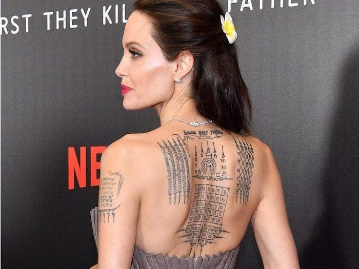 red carpet event spiritual tattoos angelina jolie back tattoos different symbols and sayings black background