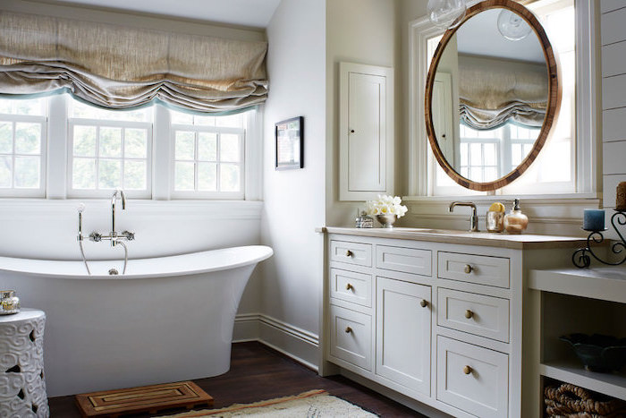 round mirror above white vanity with sink country bahtoom ideas white walls wooden floor with rugs white bath