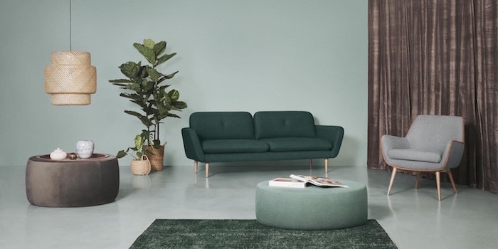 scandinavian design dark green sofa gray armchair light freen walls and floor two ottomans