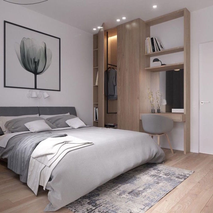 scandinavian furniture wooden wardrobe framed art above bed with gray bed sheets wooden floor small rug in front of the bed