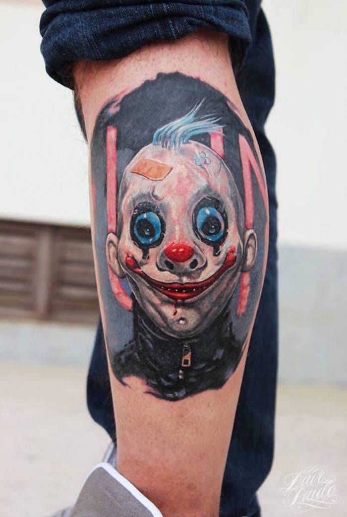 scary tattoo on the side of the leg sleeve tattoo ideas for men man wearing mask of a clown on black background