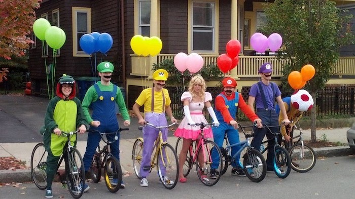 seven people dressed as characters from the super mario franchise funny diy halloween costumes mounted on bikes with balloons