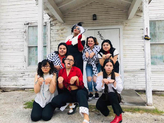 seven women dressed as cruella de ville and the dalmations halloween costumes for 3 people photographed in front of spooky house