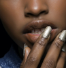 short acrylic nails gold foil crumbled on medium length almond nails on woman touching her lips