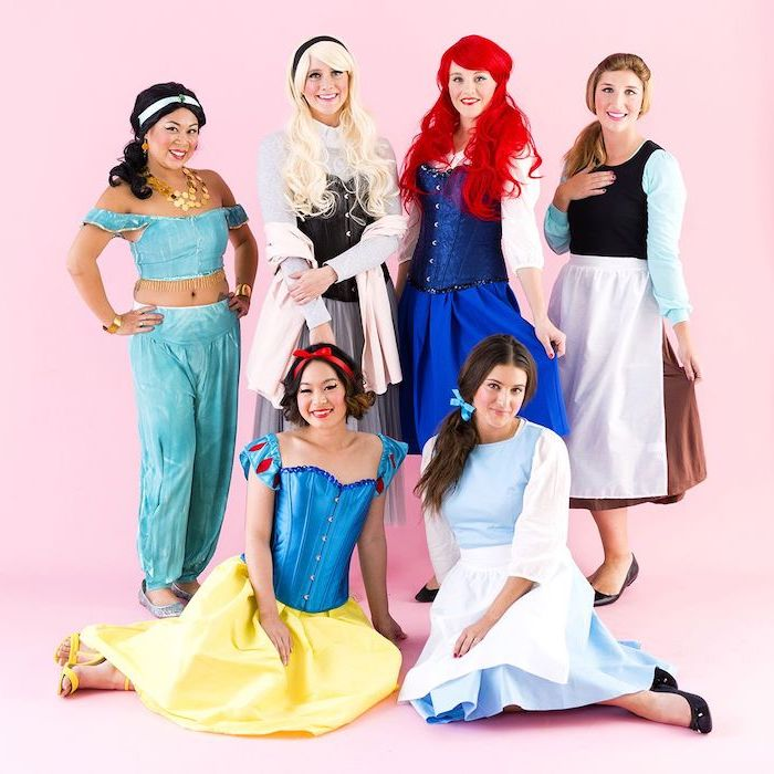 six women dressed as different disney princesses photographed in front of pink background group halloween costume ideas