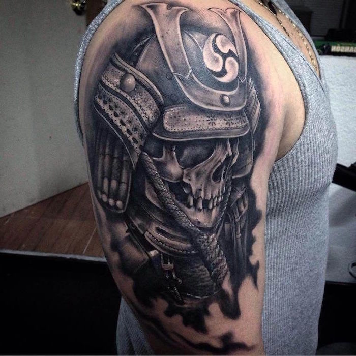 skull with armor shoulder tattoo made with black ink on man wearing gray tank top tattoo ideas for men