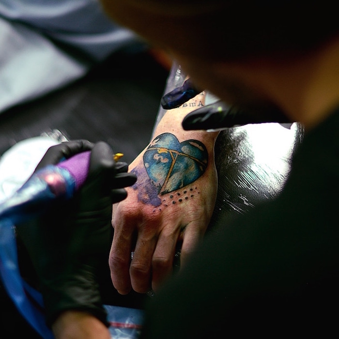 sleeve tattoo ideas for men hand tattoo of watercolor heart with blue sky with clouds inside it being tattooed by man wearing black gloves