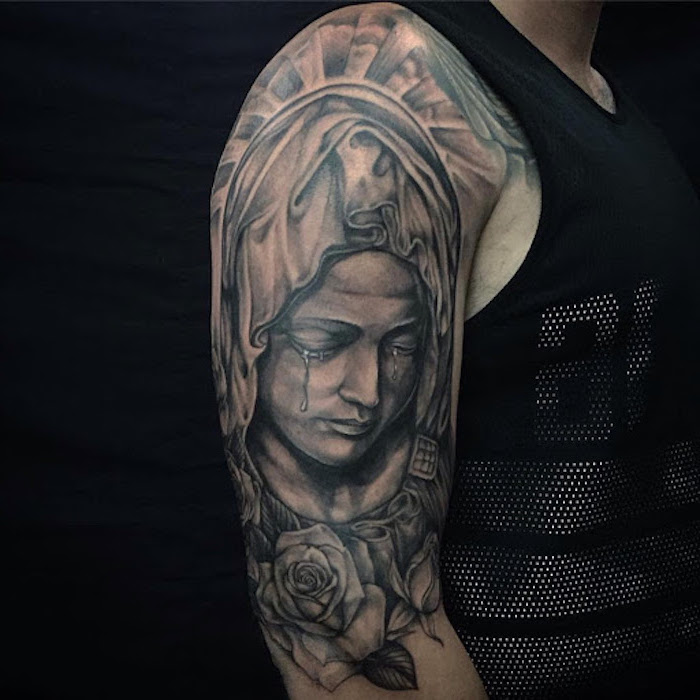 sleeve tattoo of crying virgin mary tattoos with meaning of life man wearing black top black background