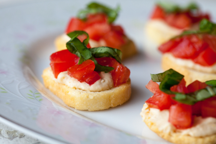 small bruschetinni with hummus chopped tomatoes and basil on top vegan party food arranged on white plate