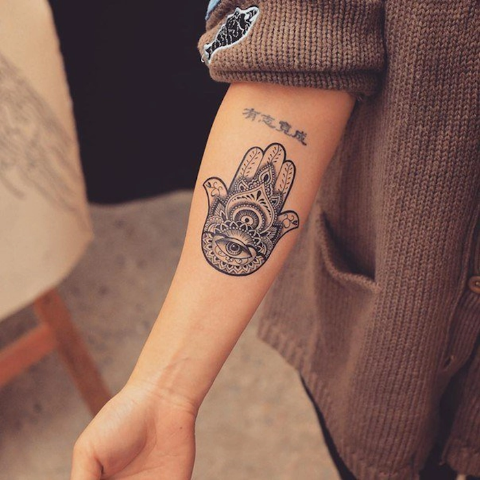 spiritual tattoos black and white hamsa hand forearm tattoo on woman dressed with brown knitted cardigan