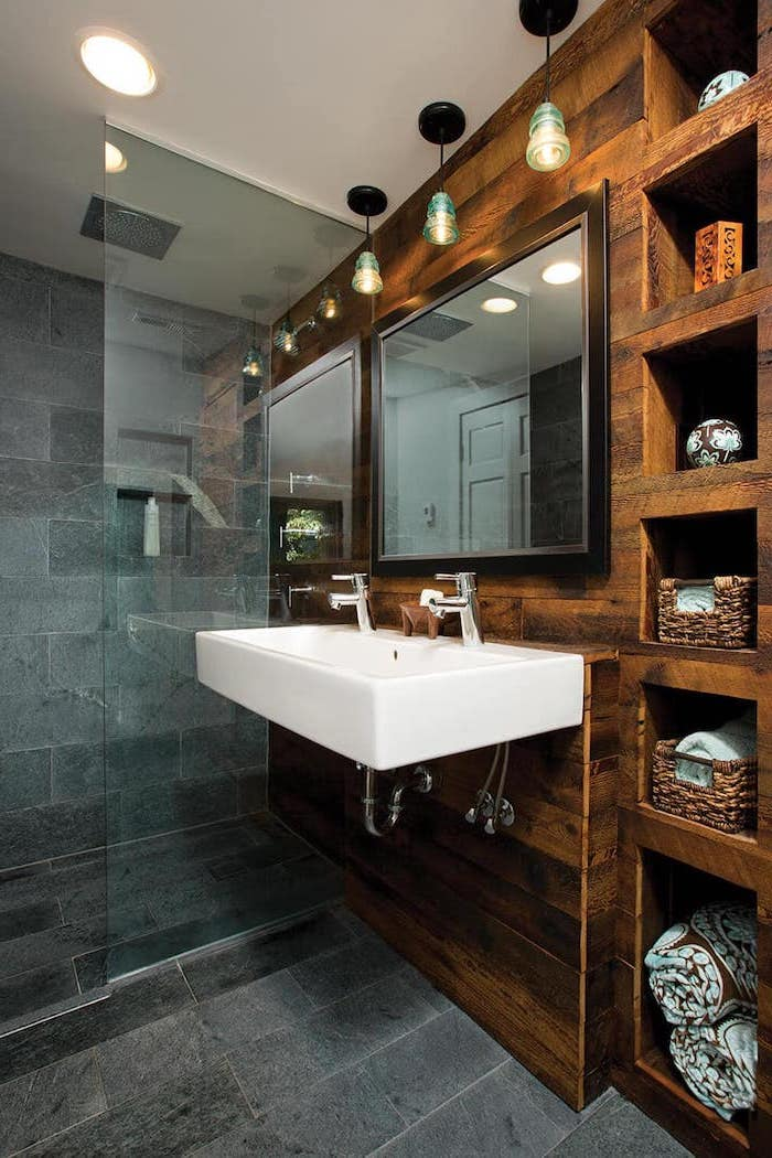 stone tiles on the floor and in the shower wooden wall with shelves around floating sink with two faucets rustic bathroom decor large mirror