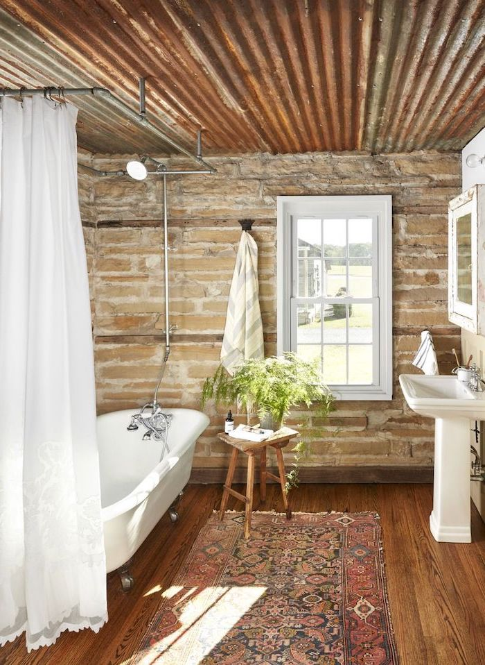 stone walls wooden floor with rug farmhouse bathroom tile white curtain around bath wooden table next to it