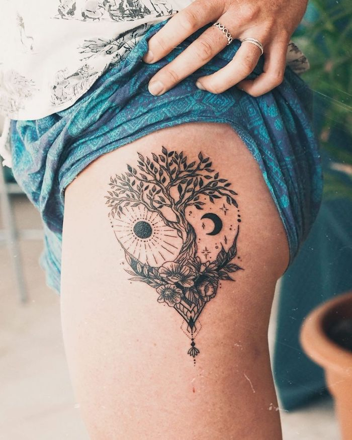 strength symbol tattoo tree of life tattoo with moon and sun on the side of the hip on woman wearing blue shorts