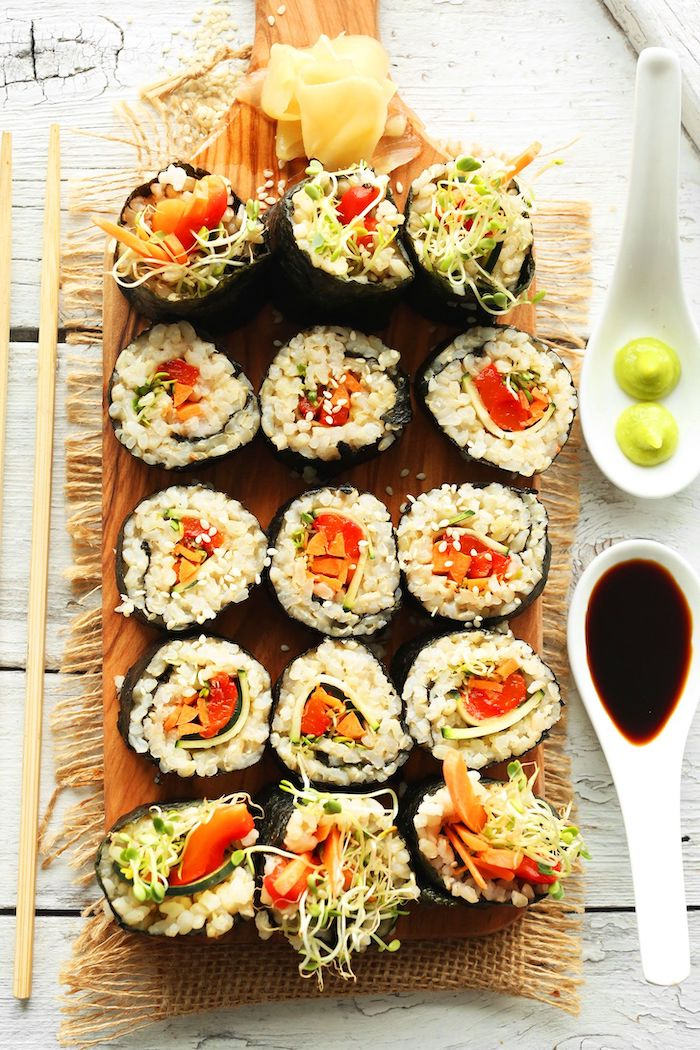 sushi with brown rice tomatoes carrots sprouts best vegan appetizers arranged on wooden cutting board