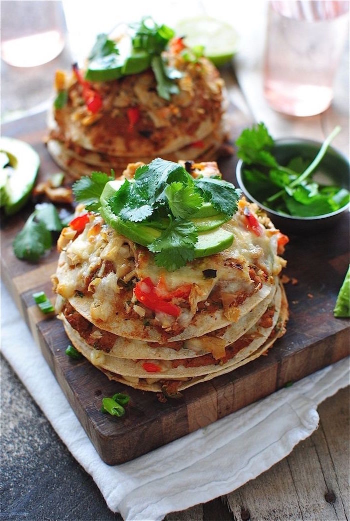 tacos placed on wooden cutting board mexican dishes garnished with avocado slices and fresh parsley