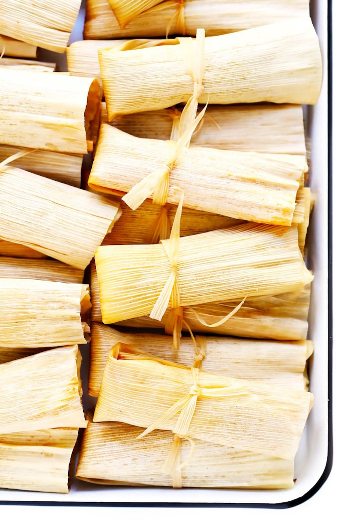 tamales wrapped in corn husk arranged in white baking sheet popular mexican food