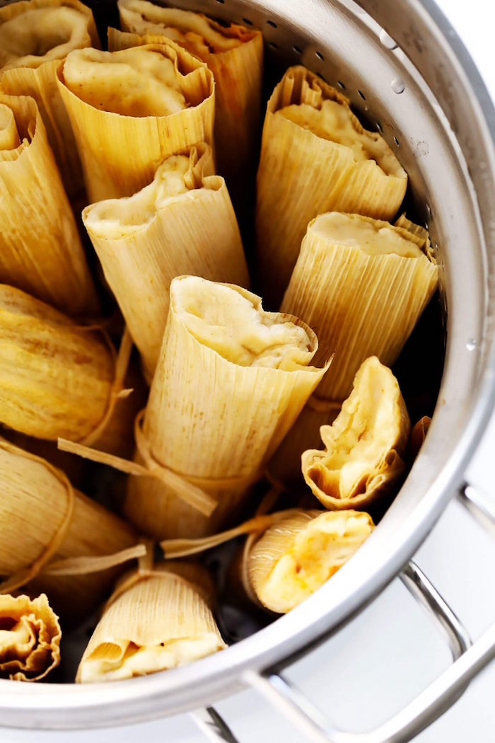 tamales wrapped in corn husk arranged inside silver pot best mexican dishes placed on white surface