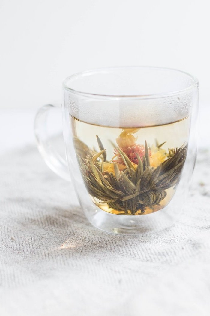 tea with different herbs inside a glass how to detox your body placed on white surface