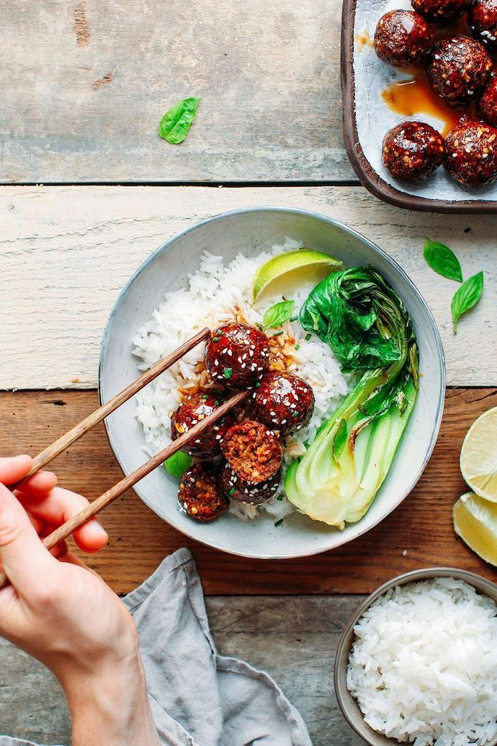 teriyaki meatballs with white sesame seeds vegan party appetizers placed in white rice in white ceramic plate lime wedges on the side