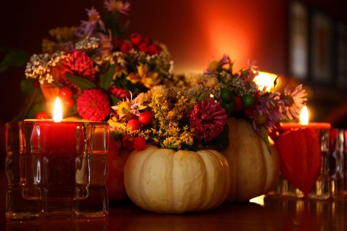 thanksgiving wallpaper table arrangement with carved out pumpkins with flowers in them surrounded by candles