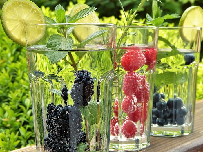 three glasses filled with water best detox drink one glass with blackberries one with raspberries one with blueberries